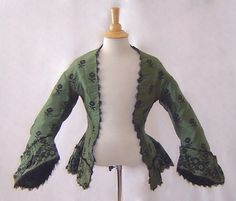 Lady's Civil War Era Silk Floral Jacket, c. 1860  This is a lady's original Civil War era jacket, c. 1860's.  This item was deaccessioned from the Brooklyn Museum of Art, New York and has the museum's acquisiton number tag sewn inside of jacket's neckline.  Beautiful black and green silk with flora pattern.  There is soft, silk, looped fringe around pagoda sleeves.  The dropped shoulder seams are a quintessential characteristically of the Civil War era bodice.