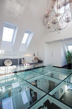 This clear glass flooring system makes an impact in this loft area. I like the contemporary look of the floor with the traditional look of the chandelier.