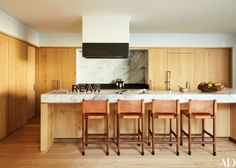 The kitchen island is topped with honed Mont Blanc marble | archdigest.com