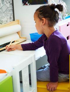 Blick auf Letitia, die mit MÅLA Zeichenpapierrolle an ihrem Schreibtisch sitzt und zeichnet.