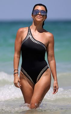 Kourtney Kardashian gives a pose on 4th of July sportin' an asymmetrical swimsuit and shield-inspired shades.