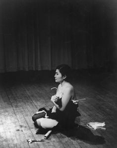 """Yoko Ono, Cut Piece, (1964)  •Ono sits on stage. Audience is invited to come and cut pieces of her clothing off.  •Event is timed- Ono has a stop watch. A la cage.. the way in which the score performs you.  •""""I wanted to do a piece in which I was more connected with people""""  •Piece was taken politically- Japanese woman sitting silently and being assaulted. Feminist."""