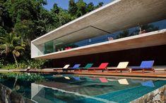 Criada para ser uma extensão da praia, a piscina conta com espreguiçadeiras coloridas de Sérgio Rodrigues. Foto: Divulgação