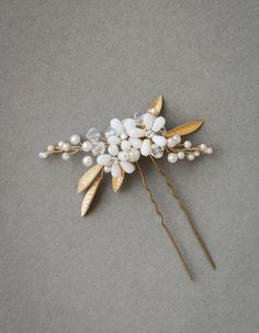 The Posie hair pin is a charming piece to add a hint of luxurious feminine appeal to any bridal look. Featuring golden and ivory tones...