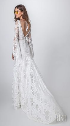 "Rish Bridal 2018 ""Sun Dance"" Collection – Romantic Bohemian Rustic Chic Wedding Dress. ALMA, a romantic bohemian sheath bridal gown with bell sleeves and bow tie at the V-neckline. The bodice and skirt are made from a crochet lace delicately beaded with Swarovski gems for a touch of glam. #RishBridal #SunDance #AlmaByRish #Sponsor #BohoBride #BohoChic #BohoGown #Wedding #WeddingDress #Bridal #WeddingGown #Bride #Romantic #WeddingDresses"