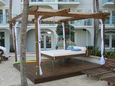 Hängebett mit Holzkonstruktion und weißen Vorhängen für Schatten