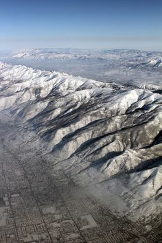 """From the air, the Wasatch fault zone, on the edge of Salt Lake City, shows many features indicative of recent earthquakes. These features include a straight and abrupt mountain front, faceted spurs, and wineglass canyons."" Caption from link"