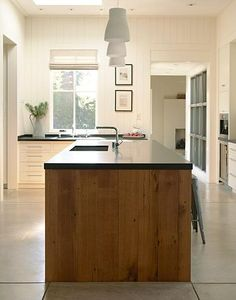Linsteadt balanced the stainless steel appliance wall with an elegantly proportioned island clad in reclaimed oak. The concrete floors are stained in Winter Beige from Chromix and coated with a high gloss finish.