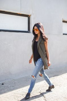 An olive vest over a tank top, destroyed jeans, and ankle boots