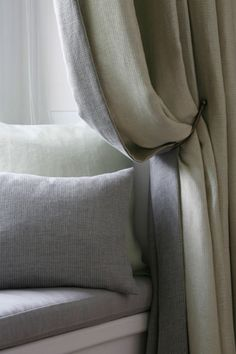 Gentle grey colour scheme showing curtain with contrast leading edge. Relaxed curtains on windows facing out to trees will give warmth and texture to the room