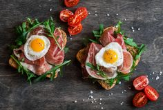 sandwich with prosciutto arugula and fried quail eggs on wooden top