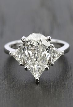 This stunning Three-Stone Trillion Engagement Ring with Pear Diamond Center features a 3.11 carat center stone!