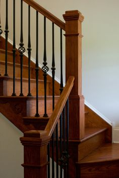 L-shaped stair with stained hand rail, posts, risers, and treads, and wrought iron decorative balusters. Painted Stair Railings, Wrought Iron Stair Railing, Wrought Iron Decor, Staircase Railings, Painted Stairs, Banisters, Staircase Design, Stairways, Black Staircase