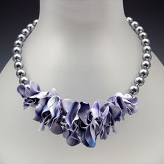 This necklace is a stack of waves suspended on a strand of lavender glass beads. The ends of the wave are connected with a silver clasp. Created by Linda Garbe