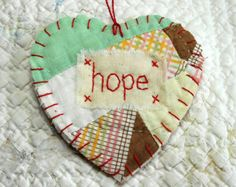 This sweet Wordz From the Heart Snippet is cut from an old quilt piece with a word of encouragement stitched on it. It is edge finished with hand stitching and completed with a scarlet hanger. Each Heart Snippet comes with a scripture verse tag and sweet red cardstock heart attached to the hanger. Picture of tag and verse is representative only. I use only vintage cutter quilts here at Wordz of Life. Each quilt has been ruggedly loved over the years and so this Snippet may be faded…