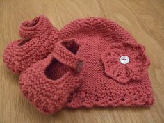 """""""Pretty, dainty shoes knitted in a lacy pattern with contrast garter stitch soles and uppers and fastened with a tiny natural mother of pearl button. The hat is a simple pull-on design worked in garter stitch and edged with the same lacy pattern as the Mary Jane-style bootees, and a shell edging. Both are made in fine milk cotton yarn."""""""