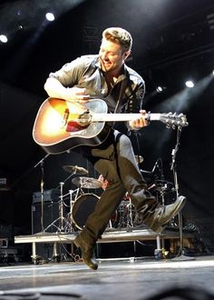 Chris Young strides across the stage while performing at the LINQ in Las Vegas on April 5, 2014.