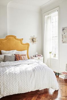 White, textured chevron duvet for the bed bed in the bedroom. A neutral, cozy layer. Chevron pattern is both traditional and modern. The Yellow, velvet upholstered headboard is so striking as well!