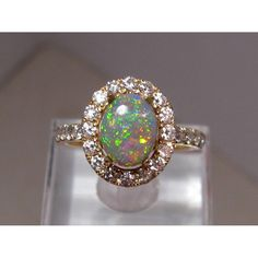 A beautiful opal ring in 14k gold with a 1.5 carat Lightning Ridge semi black opal surrounded by a halo of 2 mm diamonds and diamonds on the band.  Total diamond weight is .78 carats.