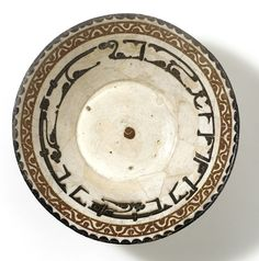 """The inscription on this bowl reads, """"Generosity is a disposition of the dwellers of Paradise."""" The letters are horizontally elongated to fit the available space.  Iran, Nishapur.  10th century.  Kufic script."""