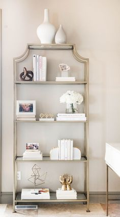 Even going semi-monochromatic with the styling on the bookcase and using lighter hues would create a lot of impact against the dark walls