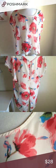 Torrid blouse Beautiful blouse! It's a cream colored blouse. It has red and blue flowers on it. Rounded neckline. It has buttons down the back. 100% polyester. Sheer. Has a tiny run in the fabric near the shoulder. torrid Tops Blouses