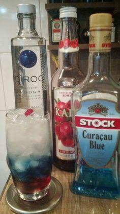 * FIRECRACKER * - 40 ml. Vodka - 40 ml. Licor Curaçau Blue - 30 ml. Suco de Limão Tahiti - 25 ml. Xarope de Grenadine - 15 ml. Xarope de Açúcar - 01 Cereja (para decoração) - Coloque o xarope de grenadine em um copo Collins, encha-o de gelo e adicione o licor curaçau blue. - Coloque a vodka, o suco de limão e o xarope de açúcar em uma coqueteleira com gelo e agite bem. - Sirva bem devagar sobre o licor curaçau blue. - Decore com uma cereja.