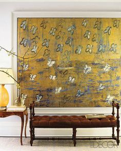 Gold Butterflies, a painting by Hunt Slonem, takes center stage in the second-floor hall, which is painted in Benjamin Moore's Seattle Gray; the English bench is antique, and the vintage side table and lamp were found in Europe.