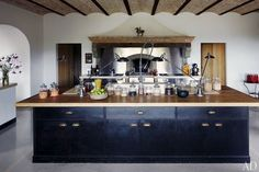 In the kitchen of architect Benedikt Bolza's Umbrian estate, the massive oak-top island features sink fittings by KWC   archdigest.com