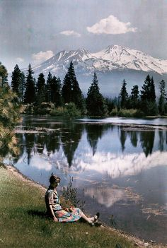 A girl sits by a lake with snow-capped mountains in the background, California, 1929. Photograph by Charles Martin, National Geographic Creative