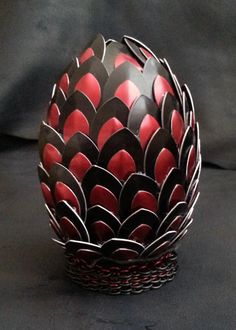 Black and red scaled dragon egg with chainmail stand on Etsy, $60.00