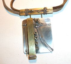 Sterling silver with brass bands, rivets, adjustable leather chords, hand signed by artist.  cskenderian9@gmail.com   $300 By Carolyn Skendarian. Love this.