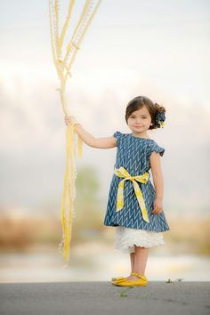 Persnickety Blue Ella Dress: A classic look for spring and summer.  We love the combination of the navy chevron print and the yellow sash - a beautiful but simplistic style. Visit littleorangefishkids.com for more info. #Persnickety #girlsclothing