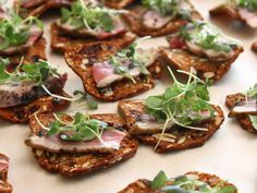 Duck Breast Pastrami on Savory Pecan, Raisin, Rosemary Toasts topped with Micro Mustard Greens