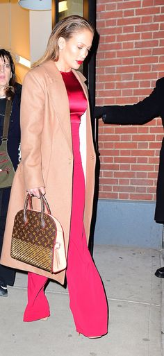Jennifer Lopez in Cushnie et Ochs top and flared trousers, House of CB coat,  Louis Vuitton's limited-edition tote and Christian Louboutin heels