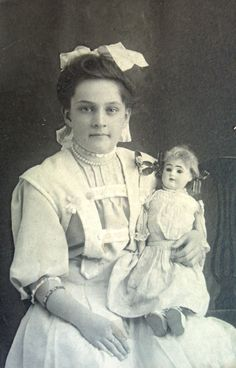 Antique photo of young girl with doll circa 1900.