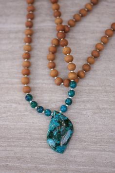 Beautiful 35mm long natural malachite with chrysocolla stone with natural matching accents and 7mm sandalwood beads. Contains 108+1 beads. Designed for meditation and yoga inspired. 33 inches. If youve ever flown over islands in a tropical sea you know the beauty of dark green against turquoise. This sight closely resembles the swirls of malachite which rest in a chrysocolla sea.  This is the appearance of malachite-chrysocolla, a crystal which has recently become one of my favorites…