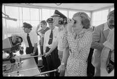 President Gerald Ford pilots a riverboat as First Lady Betty Ford looks through binoculars at a campaign stop in the South, September 1976