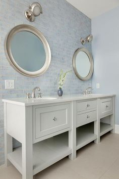 Blue and gray bathroom features a light gray dual washstand with shelf topped with light gray quartz fitted with his and hers sinks and satin nickel faucets under round silver mirrors illuminated by nautical sconces lining a blue brick tiled backsplash.