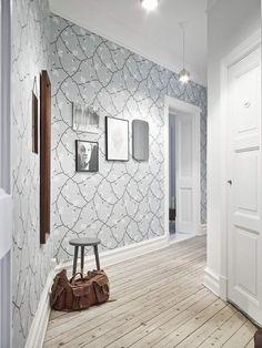 Интерьер коридора прихожей с нежным узором на светлых обоях