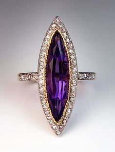 A Vintage Amethyst and Diamond Ring circa 1930. A Platinum topped 18K Gold navette shaped ring set with a marquise-cut Amethyst in a milgrain Gold bezel, bordered by numerous old rose-cut diamonds set in Platinum over gold. Flanked by rose-cut Diamond shoulders. The ring is marked with French import marks for 18K Gold and 950 Platinum.