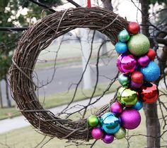Ghirlanda natalizia fai da te con rami intrecciati e palline colorate