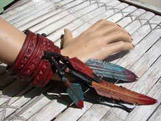 distressed pink leather wrist wrap cuff with carved tiny leather feathers turquoise/red. $78.00, via Etsy.