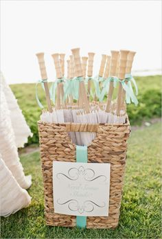 Parasols at the ready. Ribbon tied around each handle carries out the color theme.