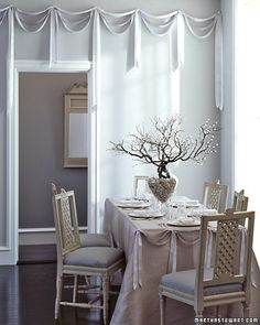 Silvery garlands of satin ribbon festoon walls and the reception table. In the center of the table, a large footed vase filled with river rocks holds bejeweled branches; their beads were attached by hand.
