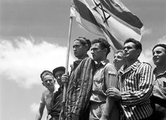 """""""Jewish survivors of the Buchenwald Nazi concentration camp, some still in their camp clothing, stand on the deck of the refugee immigration ship Mataroa, on July 15, 1945 at Haifa port, during the British Mandate of Palestine, in what would later..."""