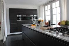 Zwart eikenkleurige keuken met spoel/- kookeilend en zwevende kastenwand volledig verzonken in bouwkundige nis — in Waalre.