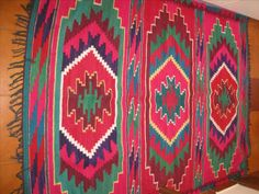 This is an antique traditional Romanian woven wool carpet / rug with geometrical pattern . Absolutely stunning and vivid colours . Hand woven in Transylvania 60-70 years ago .   Hand woven with wool on cotton thread foundation .