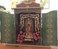 Oratório grande pintado nas cores verde, marrom, vermelho e detalhes dourados.