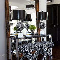 table in front of floor mirror